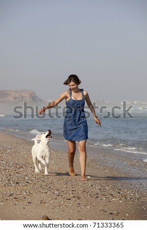 Young woman running and playing with her cute labrador retriever puppy