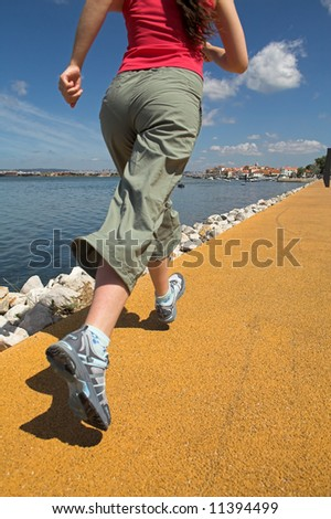 Young woman running by seaside - stock photo