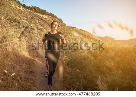 Young woman running down a mountain in full sun light with drying grass behind her while wearing black and grey