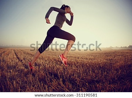 Young woman running fast on field during sunrise - stock photo