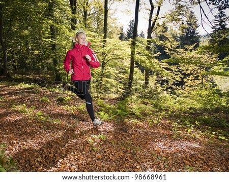 Young woman running in forest close up - stock photo