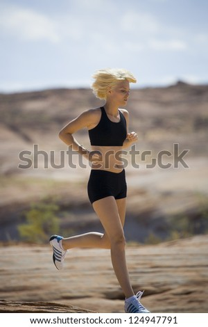 Young woman running in landscape