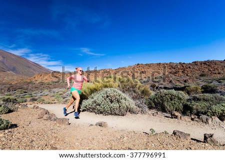 Young woman running in mountains on sunny summer day. Beauty female runner jogging and exercising outdoors in nature, trail running training on rocky trail footpath on Tenerife, Canary Islands - stock photo