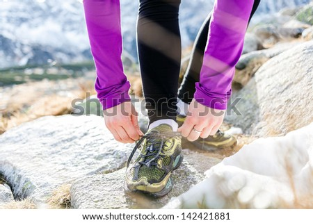 Young woman running in mountains on winter fall sunny day. Motivation and inspiration fitness concept. Female runner tying sport shoe and exercising outdoors in nature, sunset. - stock photo