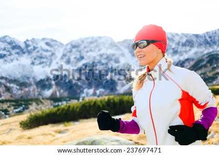 Young woman running in mountains on winter or fall sunny day. Happy beautiful female runner exercising outdoors in nature, using black sunglasses for sunset. Healthy lifestyle outside adventure. - stock photo