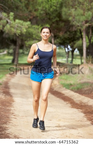 Young woman running in park - stock photo