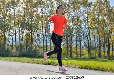 young woman running in the park, listens to music and enjoys - stock photo