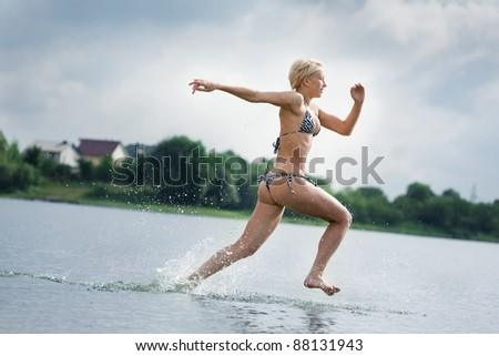 young woman running in the water - stock photo