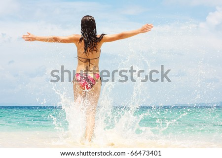 Young woman running into ocean - stock photo
