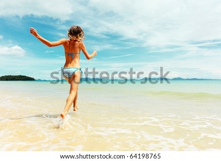 Young woman running into sea - stock photo