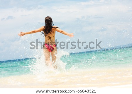 Young woman running into water - stock photo
