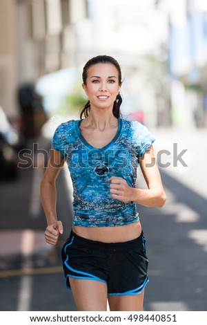 Young woman running jogging on downtown street