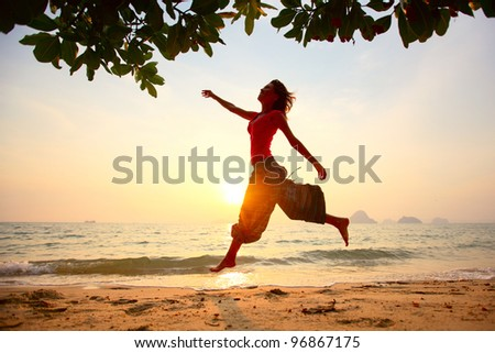Young woman running on a beach at sunset