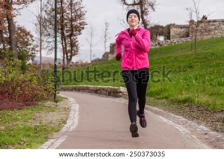 Young woman running on a cold winter day in an urban park. - stock photo