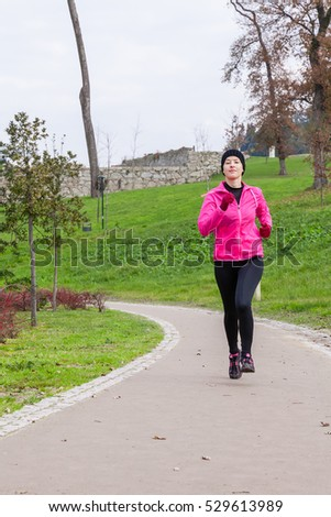 Young woman running on a cold winter day on an urban park.