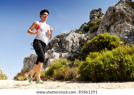 Young woman running on a dry mountain path.