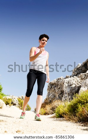 Young woman running on a dry mountain path. - stock photo
