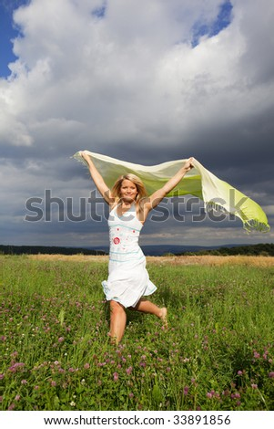 Young woman running on a green meadow