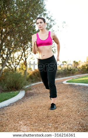 Young woman running on a path in a park - stock photo