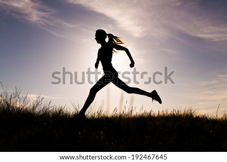 Young woman running on a rural road during sunset
