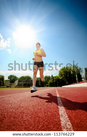 Young woman running on a track.