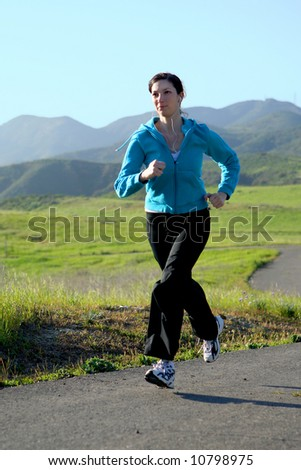 Young woman running on a trail - stock photo