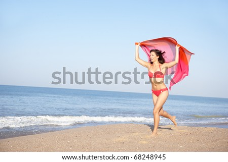 Young woman running on beach - stock photo