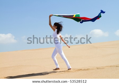young woman running on beach and holding a south african flag - stock photo