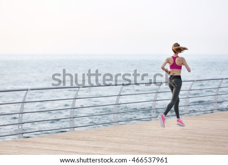 Young woman running on pier