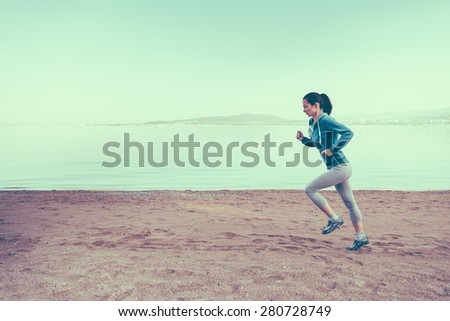 Young woman running on sand beach near the sea in summer in the morning. Concept of sport and healthy lifestyle. Space for text in the left part of image. Image with instagram filter