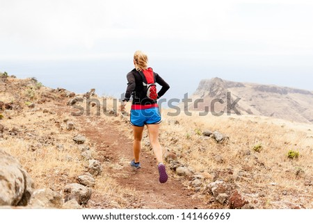 Young woman running on trail in mountains on summer day. Female runner exercising outdoors in nature on La Gomera, Canary Islands. - stock photo