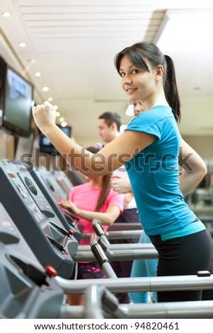 young woman running on treadmill at gym, looking at camera - stock photo