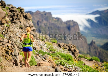 Young woman running or power hiking in mountains on sunny summer day. Beauty female runner jogging and exercising outdoors in nature, rocky trail footpath on La Palma, Canary Islands - stock photo