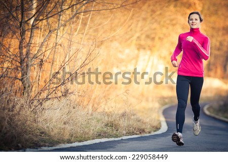 Young woman running outdoors in a city park on a cold fall/winter day - stock photo