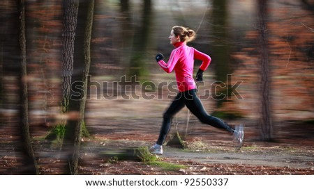 Young woman running outdoors in a city park on a cold fall/winter day (motion blurred image) - stock photo