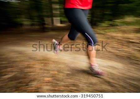 Young woman running outdoors in a forest, going fast (motion blurred image) - stock photo