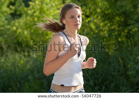 Young woman running outdoors in green park on sunny summer day - stock photo