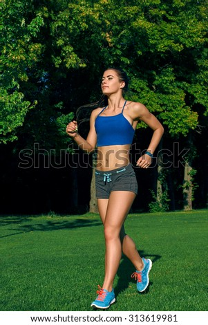 Young woman running outdoors on a lovely sunny summer evening  - stock photo
