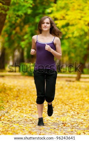 Young woman running outdoors on a lovely sunny winter (fall) day - stock photo