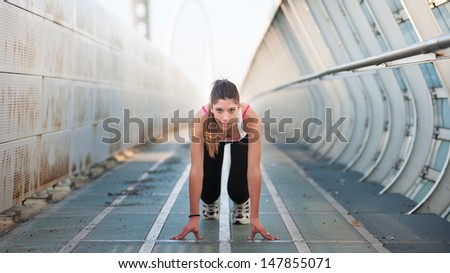 Young woman running outdoors on a modern bridge.  - stock photo