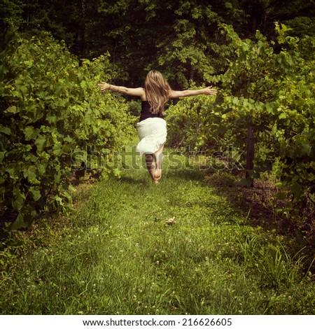 Young woman running through a vineyard - stock photo