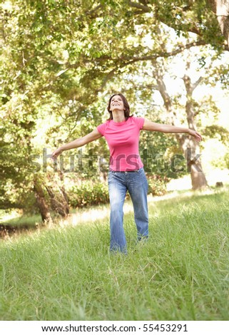 Young Woman Running Through Long Grass In Park - stock photo
