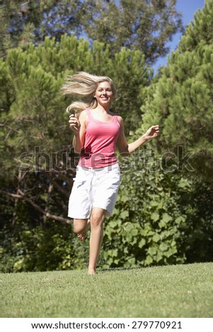 Young Woman Running Through Summer Field