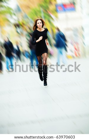 young woman running through the city - stock photo