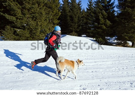Young woman running with an Akita dog in winter mountains - stock photo