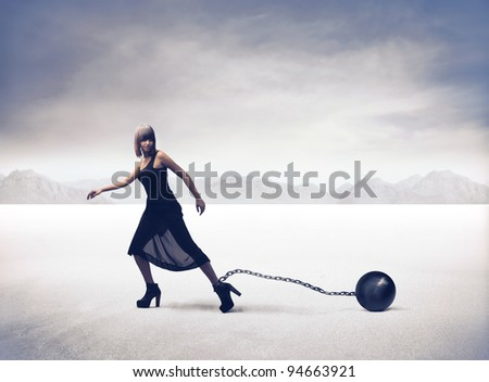 Young woman running with an iron ball tied to her ankle - stock photo