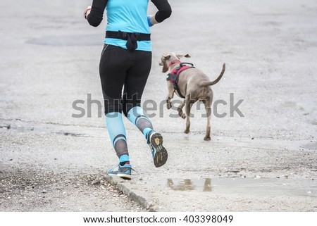 Young woman running with dog in the city street - stock photo