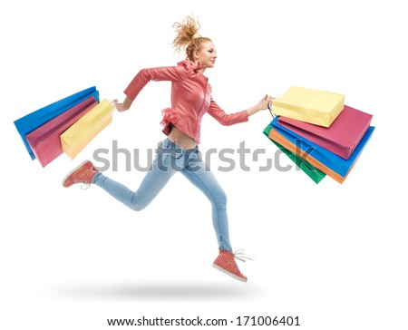 young woman running with shopping bags in hands - stock photo