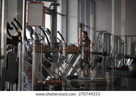 young woman runs on a treadmill, exercise in the sport club - stock photo