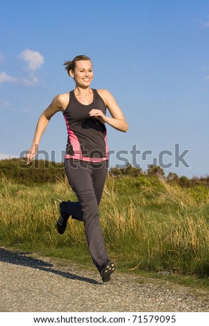 young woman runs  outdoor in a park - stock photo